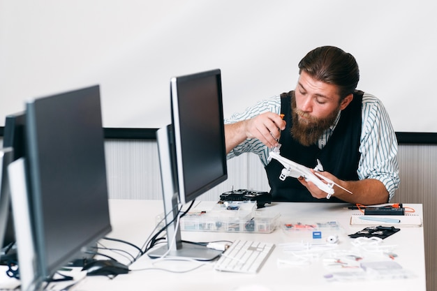 Bearded master disassembling drone. portrait of young hipster office worker repairing unmanned aerial vehicle at work. hobby, handyman, electronics concept