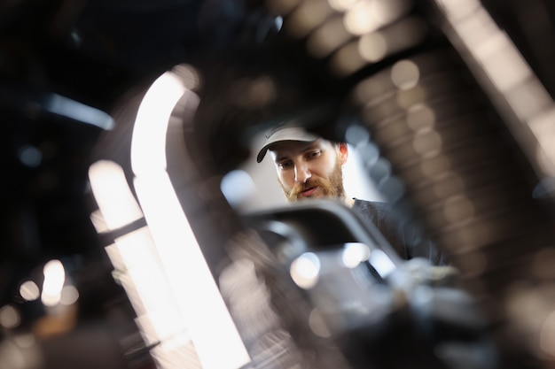 수염 난 마스터 자물쇠 제조공이 오토바이 엔진 자동차 수리점 개념을 살펴봅니다.
