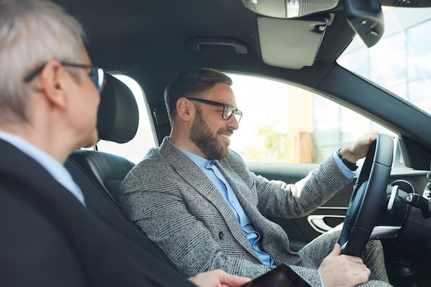 Bearded mature businessman in eyeglasses driving car and talking to mature businesswoman