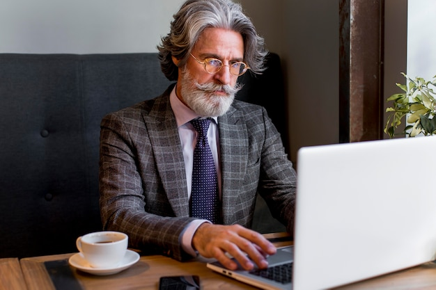 Bearded mature male working on laptop