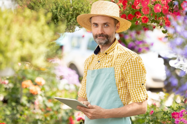 Bearded mature man in apron and hat scrolling in touchpad while surfing in the net for information about new plants