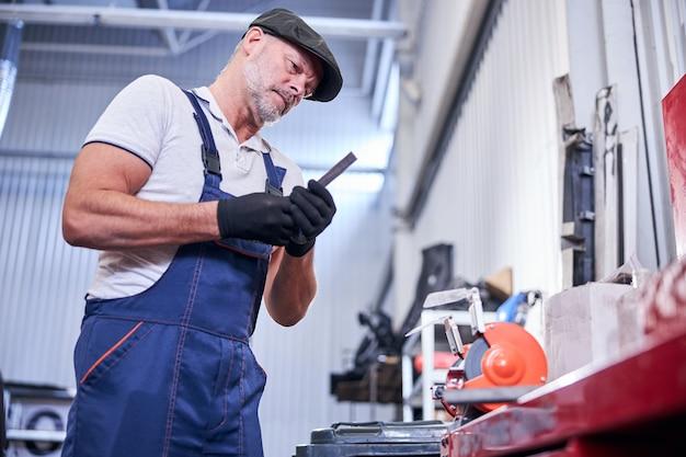 Bearded mechanic grinding and polishing metal in garage