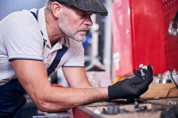 Бородатый механик в перчатках держит серебряные болты