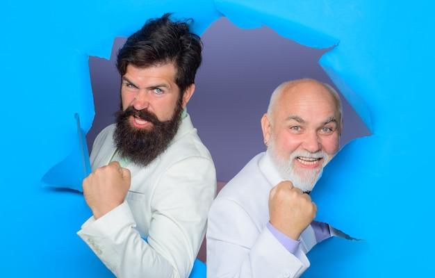 Bearded men peeking from ripped paper hole discount sale season sale copy space men making hole in