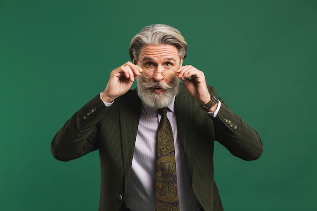 Bearded middle age teacher in suit holds glasses with his hands and blinks his eyes with fun on green wall
