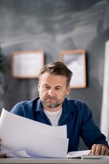 カジュアルな服装でひげを生やした中年の建築家がオフィスで働いている間、机でスケッチを使って青写真を見て