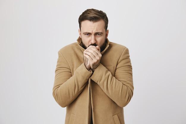 Бородатый мужчина средних лет мерзнет на улице