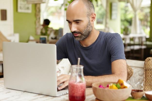 Бородатый самозанятый мужчина средних лет сидит в кафе перед обычным ноутбуком и серьезно и сосредоточенно смотрит в экран, работая удаленно над своим проектом, используя бесплатный wi-fi
