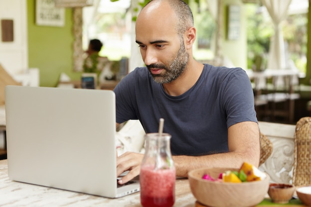 Bearded middle-aged self-employed man sitting at cafe in front of generic laptop and looking at screen with serious and concentrated expression while working remotely on his project, using free wi-fi