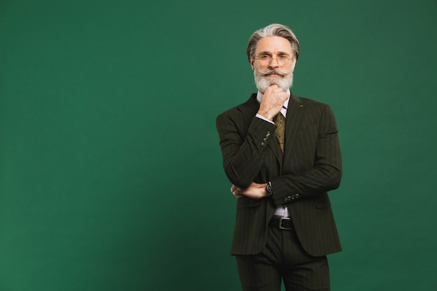 A bearded middle-aged teacher in suit holding a beard and thinking on a green wall with copy space