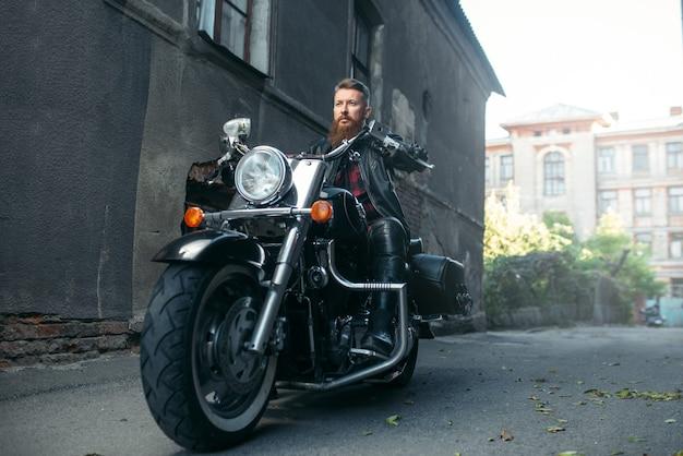 Бородатый мотоциклист позирует на классическом чоппере