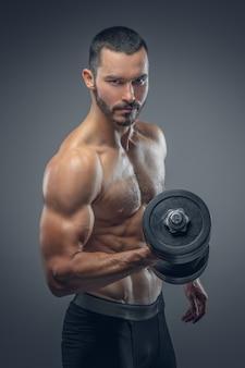 Bearded muscular male holds dumbbell.