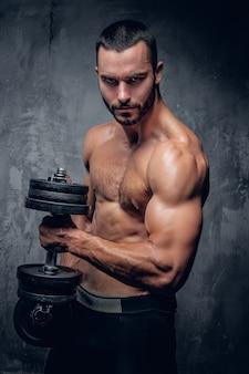 Bearded muscular male holds dumbbell