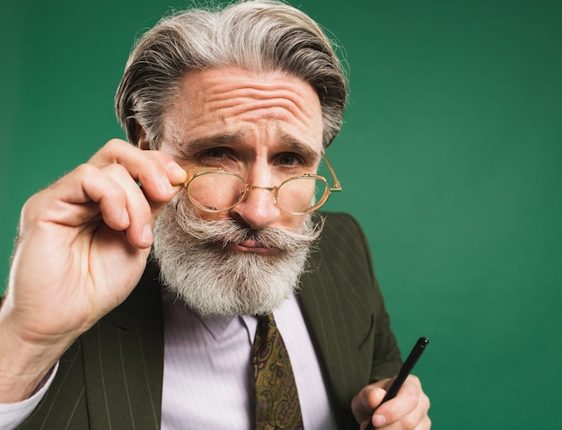 Bearded and mustachioed middle-aged teacher in suit holds hand with glasses and looks closeup on green wall