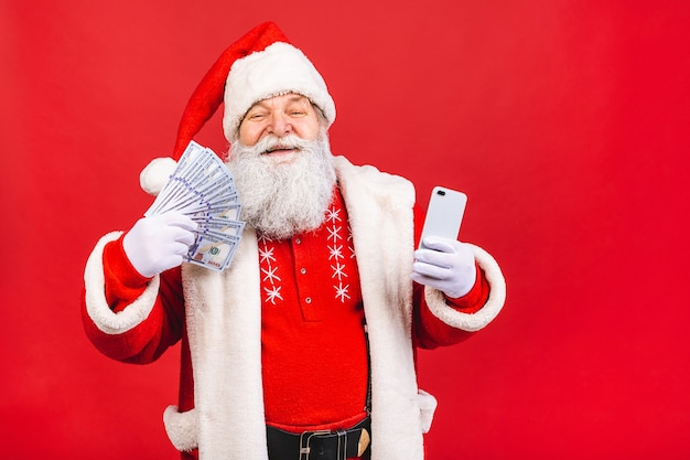Bearded old man in santa claus costume holding a mobile phone an money standing isolated on red background