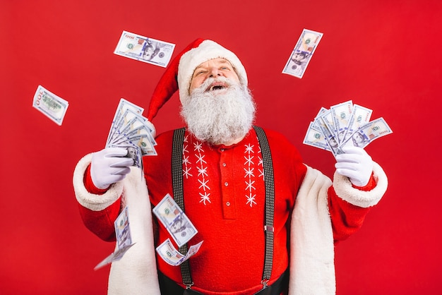 Bearded old man in santa claus costume holding money standing isolated on red background