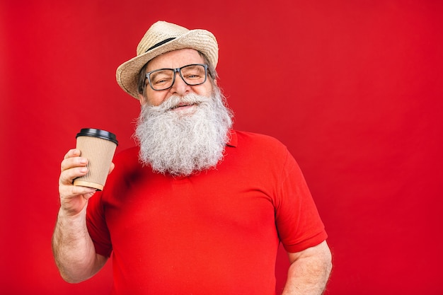 Бородатый старик в очках и шляпе держит чашку кофе на красном фоне