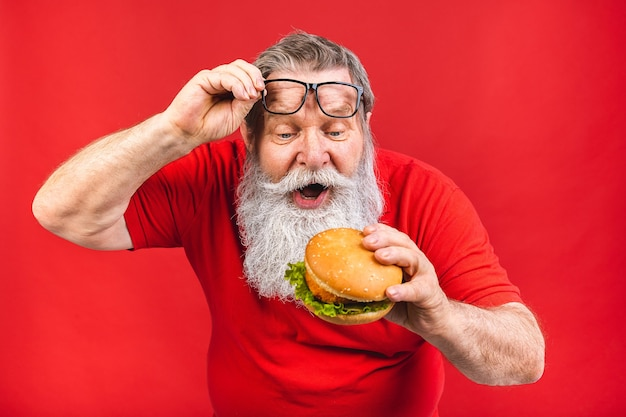Bearded old man with glasses in red tshirt eating a hamburger isolated on red background