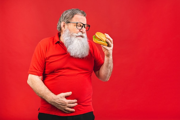 Bearded old man with glasses in red tshirt holding a hamburger isolated on red background