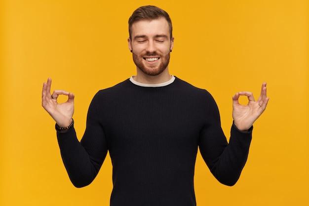 ひげを生やした平和な男、ブルネットの髪の穏やかな男。ピアスあり。黒のセーターを着ています。瞑想。目を閉じてリラックス。立って、黄色の壁に孤立した笑顔