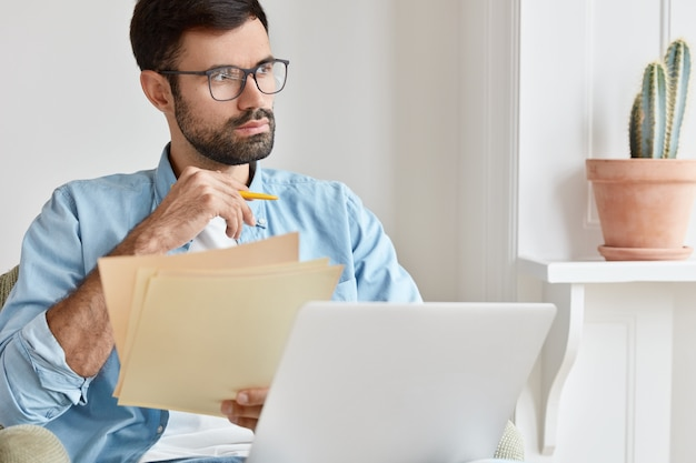 Bearded pensive man works from home, counts financial data, holds paper documents