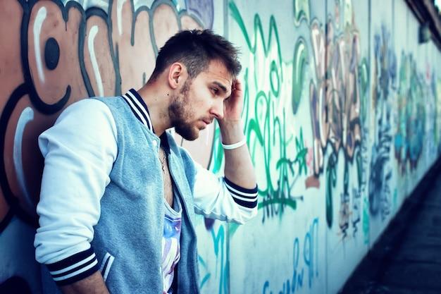 Бородатый человек возле стены граффити