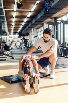Bearded personal trainer helping woman to stretch. woman sitting on mat.