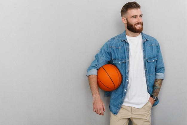Bearded pleased man in denim shirt holding basketball and smiling isolated over gray wall