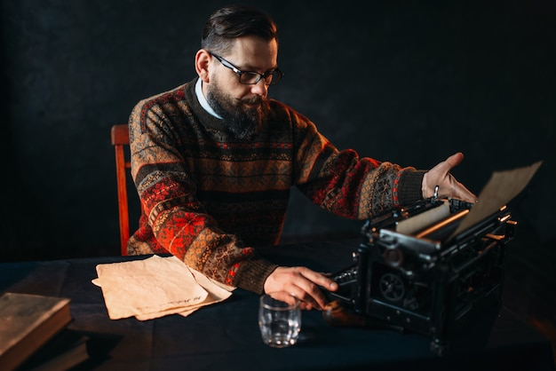 Bearded poet in glasses typing on typewriter