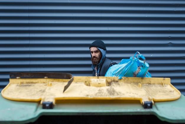 街の通りのゴミ箱で食べ物を探しているひげを生やした貧しい人々。