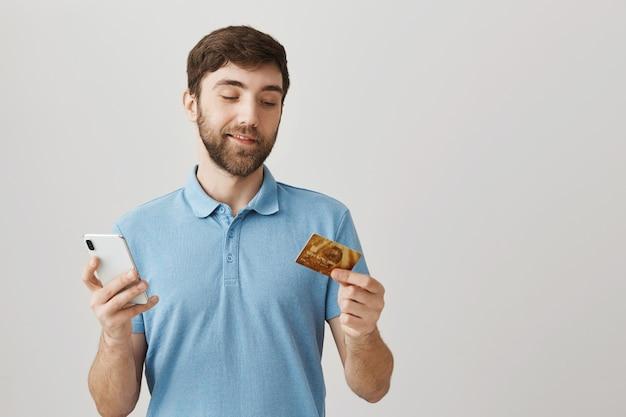 Barbuto ritratto di un giovane ragazzo con maglietta blu