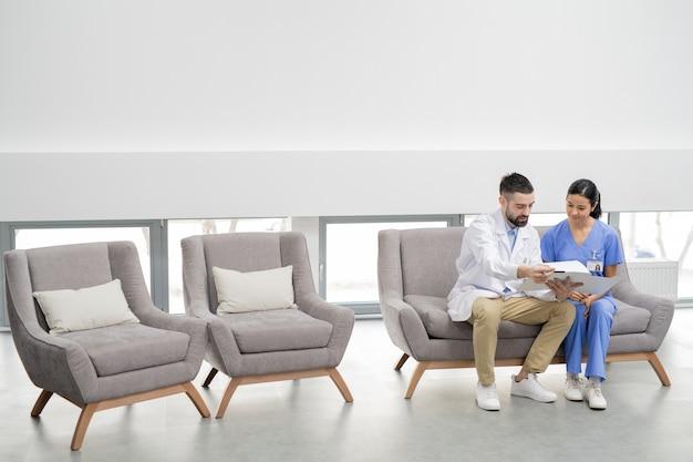 Бородатый профессиональный стоматолог в белом халате и его симпатичный молодой помощник в униформе обсуждают медицинский документ одного из клиентов