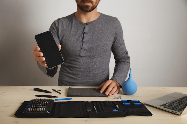 Barbuto professionista mostra riparato smartphone fisso dopo la sostituzione del servizio, sopra i suoi strumenti specifici nella borsa degli attrezzi vicino al computer portatile sulla tavola di legno bianca
