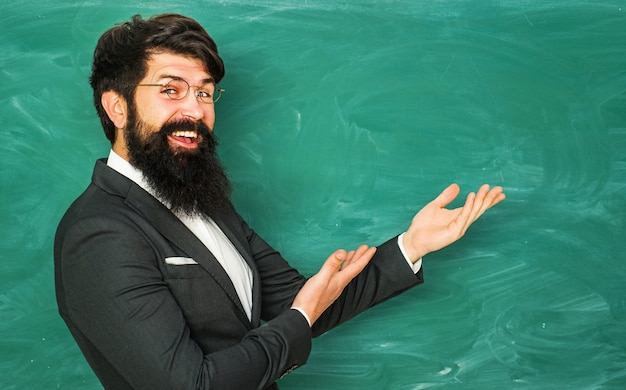Bearded professor at school teaching on chalkboard