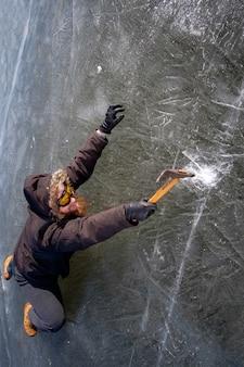 氷の岩の上に氷の斧をそりと保護黄色のメガネでひげを生やした赤毛アルピニスト