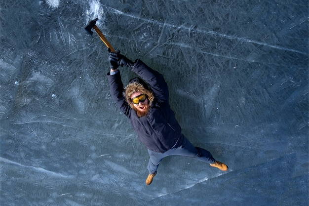 Bearded redhead alpinist in protective yellow glasses with ice axe clibing up on icy rock