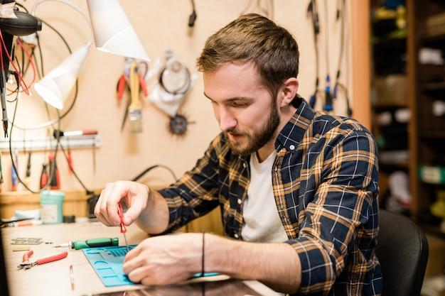 Бородатый ремонтник наклоняется над сломанным гаджетом и с помощью отвертки фиксирует мелкие детали или болты демонтированного смартфона