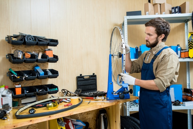 Bearded repairman concentrated on work