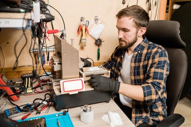 壊れたスマートフォンのトラブルを発見しようとしながら作業機材に座っている保護手袋のひげを生やした修理工