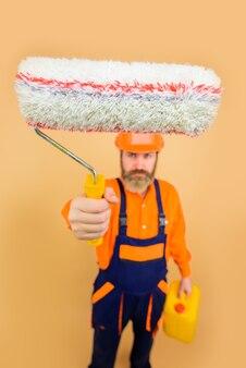 Бородатый ремонтник в униформе держит малярный валик, ремонтник, профессиональный художник-дизайнер в полный рост