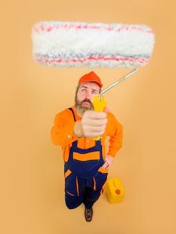 Бородатый ремонтник в униформе держит малярного валика в полный рост профессионального маляра.