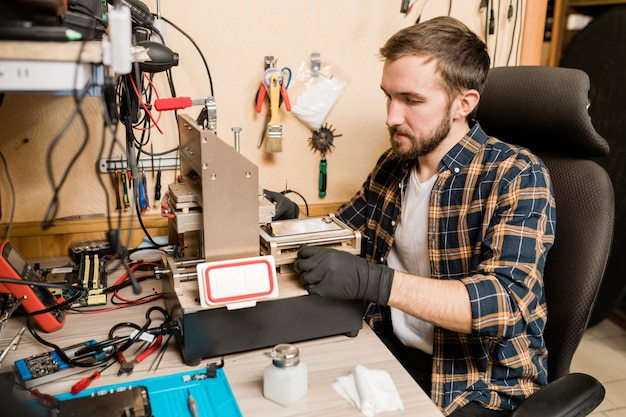 Bearded repairman in protective gloves sitting by working equipment while trying to find out trouble of broken smartphone