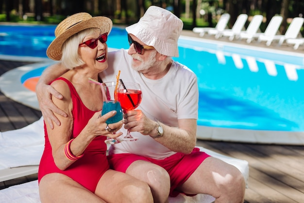 Bearded retired man hugging his beautiful beaming wife while sitting on deck chairs near the pool