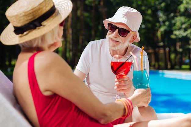 Бородатый пенсионер в летней шляпе и солнечных очках смотрит на свою красивую современную жену