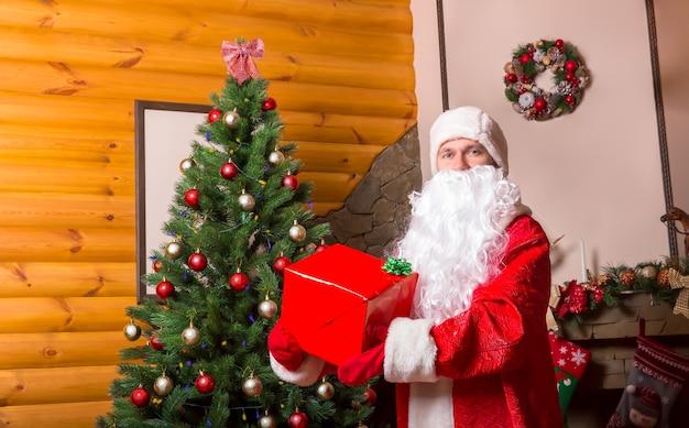 Бородатый дед мороз в красном костюме с подарочной коробкой, украшенным камином и елкой