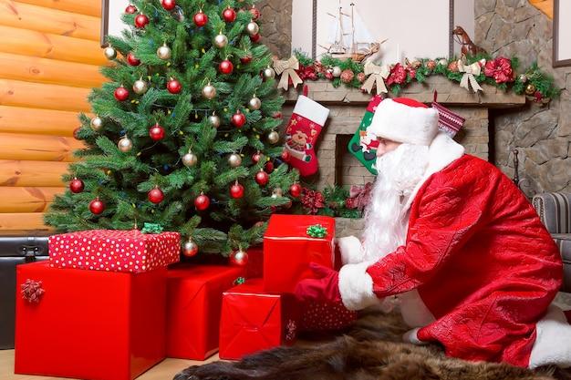Бородатый дед мороз кладет подарочные коробки под елку