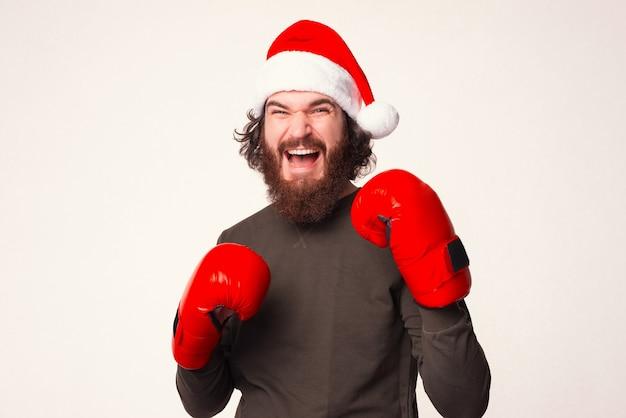 クリスマスの帽子とボクシンググローブを身に着けている間、ひげを生やした叫び声の男は、攻撃する準備ができている位置に立っています。