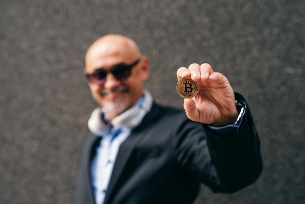 Bearded senior adult wealthy businessman holding bit-coin.