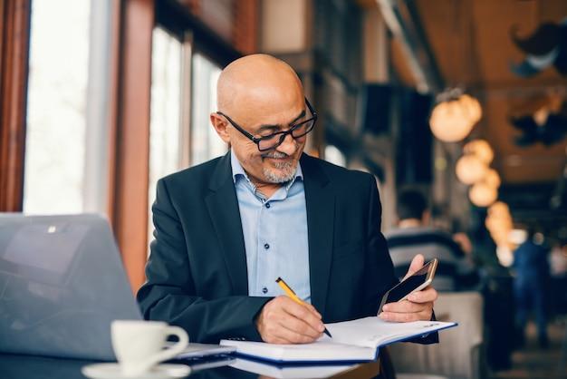 ひげを生やした上級ビジネスマンがスマートフォンを見て、カフェテリアに座っている間に議題でタスクを書きます。 Premium写真