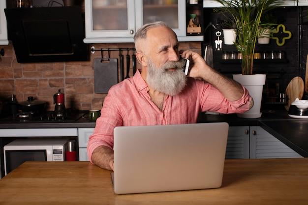 ラップトップで働くひげを生やした上級ビジネスマン